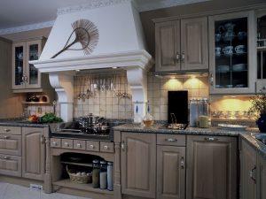 Z DUBOVÉHO masivu je kuchyň v toskánském stylu. Povrchová úprava patina bílá antik dává vyniknout přirozené struktuře masivního dřeva. Typ krbové vestavby pro odsavač par spolu s užitím motivu toskánského oblouku na masivních kazetách dvířek propůjčuje kuchyni jižanskou atmosféru. Cena zobrazeného nábytku je 290 000 Kč. HŠ RUSTIKAL