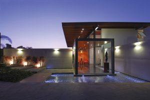 Významnou roli v exteriéru vily hrají vodní prvky. Nejenom bazén na zahradě, ale také vodní plocha originálně lemující vstupní část osvěžují ovzduší a vnášejí prvek originality.