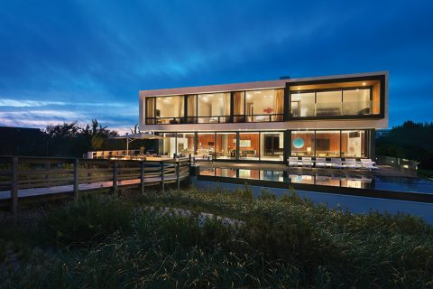 Zvláště v noci při umělém osvětlení vynikne, že velkorysý prostor domu není zbytečné svázaný stěnami. Ty jsou umístěny především tam, kde plní svůj účel – mezi ložnicemi a obytným a technickým zázemím domu. Také skleněné zábradlí kolem terasy dává domu optický prostor.