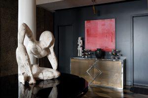 Stěna tmavé, antracitově šedé barvy působí jako kontrastní prvek vůči světle pojednanému interiéru. Komoda a plastiky na ní nás vracejí do období kubismu.