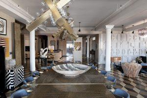 Každý kus nábytku vyzařuje vlastní energii. Stoly z mosazného plechu souzní s monstrózním kovovým lustrem, plastika sedící ženy tvoří ohnisko obytného prostoru.