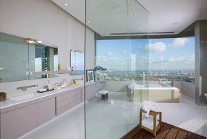 Koupelna kombinuje bílou barvu s pastelovými tóny.  Zapuštěná umyvadla v kompozitní desce beze spár odpovídají posledním trendům. Vana s masážními programy umožňuje koupel s výhledem na město.