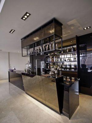 Přední strana barového pultu vzhledově koresponduje se šikmými zrcadly na stěně. Originálně řešené osvětlení zároveň slouží jako ostrůvek pro vystavení nápojového skla. Barový pult pokračuje do varné zóny