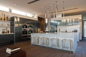 V kuchyni využili designéři kontrastu lakovaných bílých a leštěných hliníkových ploch. Barovky mají sedáky potažené bílou kůží.