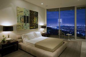 Ložnice s terasou, na které jsou vidět ikony evropského designu. Kruhový stolek od Eera Saarinena a židle Ghost od Philippa Starcka.