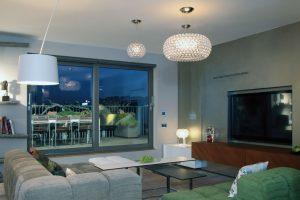 Obývací prostor přímo navazuje na velkoryse řešenou terasu. Díky proskleným stěnám je dostatečně zásoben denním světlem. Výhled do Nuselského údolí dává tomuto expresivnímu interiéru další rozměr