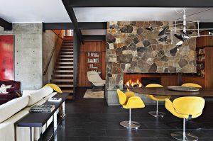Ostře narýsované linie ocelové konstrukce rozbíjí kamenná stěna, postavená z přírodního neopracovaného kamene. V popředí vynikají žluté židle Swan od Arneho Jacobsena.