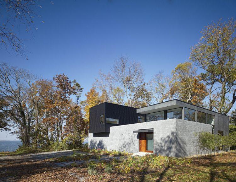 Ve všech směrech minimalistický dům byl postaven v půvabném přírodním zákoutí, na zalesněném pozemku u mořské zátoky Chesapeake, s výhledem na klidnou vodní hladinu.