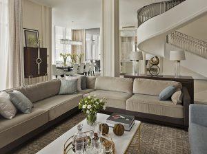 Multifunkční otevřené přízemí rezidence zahrnuje obývací zónu, jídelnu a kuchyni oddělenou prosklenými stěnami. Výrazným prvkem interiéru je monumentální schodiště. Lampy Halo od návrháře Thomase Pheasanta, stojící na komodě za pohovkou, jsou z nabídky Baker Furniture.