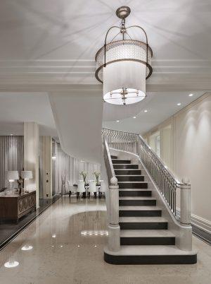 Nádherný dekorativní lustr Bracelet od Baker Furniture, který dominuje vstupní hale, dodává prostoru stylovou eleganci. Stínidlo v barvě slonové kosti obepíná v horní části prstenec s povrchem v patinované mosazi, vyplněný zavěšenými prvky ze skla.