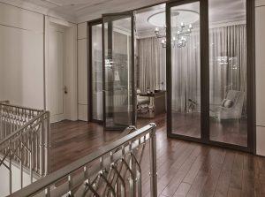 Část horní schodišťové haly se jednoduchým přepažením prostoru prosklenými stěnami a dveřmi proměnila v sice nevelkou, ale o to luxusnější domácí pracovnu.