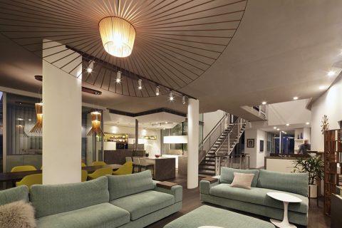 """Srdcem celého domu je centrální multifunkční společenský prostor. Jeho umírněné barevné řešení, z něhož """"vyčnívají"""" limetková křesla u jídelního stolu, vyvažuje bohatá členitost geometrické dispozice."""