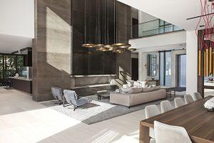 Část přízemního společenského prostoru je otevřená do druhé obytné úrovně rezidence, což ještě opticky násobí už tak velkorysou dispozici. Efekt zvýrazňuje zábradlí z čirého skla, lemující horní galerii.
