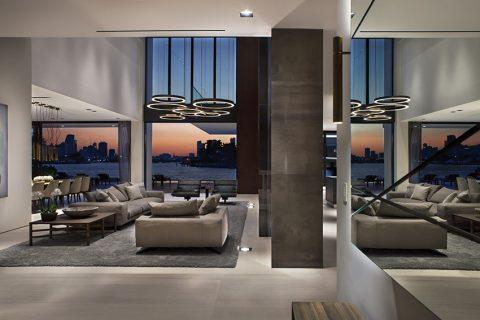 Už tak impozantní dispozici společenského prostoru, částečně otevřeného do druhé obytné úrovně s klidovým zázemím, násobí odraz ve velkoplošné zrcadlové stěně. O osvětlení této zóny se kromě lustru starají rovněž zapuštěné stropní a podlahové bodovky.