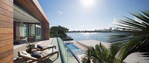 Také horní patro má k dispozici rozlehlou terasu, přímo navazující na hlavní ložnici, která se otevírá skládacími prosklenými stěnami. Výhled do zátoky a na panorama Miami Beach neruší ani transparentní zábradlí.