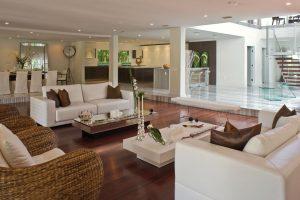 Celkový pohled na multifunkční zónu v přízemí odhaluje stylovou jednotu interiéru i soulad použitých materiálů. Industriální charakter foyer podtrhuje futuristický skleněný stolek s křeslem ze stejného materiálu