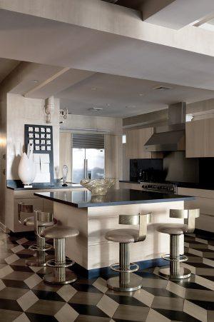 Strohé tvary geometrické kuchyně s prostorným středovým ostrůvkem změkčují organické tvary doplňků. Okrové a zlatavé a světle šedé tóny tvoří jednotící barevnou paletu interiéru.