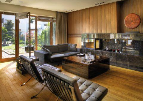 Designové evergreeny, křesílka Barcelona od Miese Van der Rohe, vtiskují interiéru noblesu a odlehčují poněkud masivní vzhled krbové stěny
