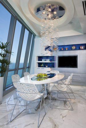 Aby interiér snídaňové jídelny nepůsobil sterilně, designéři vytvořili souhru mezi odstíny převažující bílé a akcenty modré barvy.