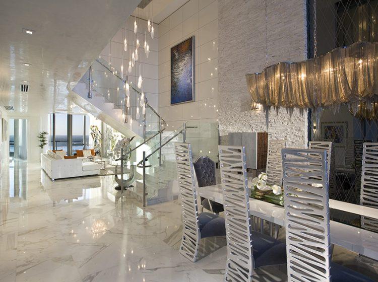Srdcem penthousu je opulentní jídelna se stropem ve výši 7,6 m. Lesklá mramorová podlaha odráží světlo designových lustrů, z nichž jeden vyplňuje schodišťové zrcadlo a druhý se vznáší nad jídelním stolem.