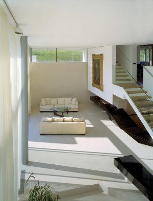 Obytný prostor výškově přizpůsobený terénu připomíná loft. Otevřené schodiště vede na otevřenou galerii, ze které se vchází do ložnic dětí, dalšího obývacího pokoje a místnosti pro hosty.