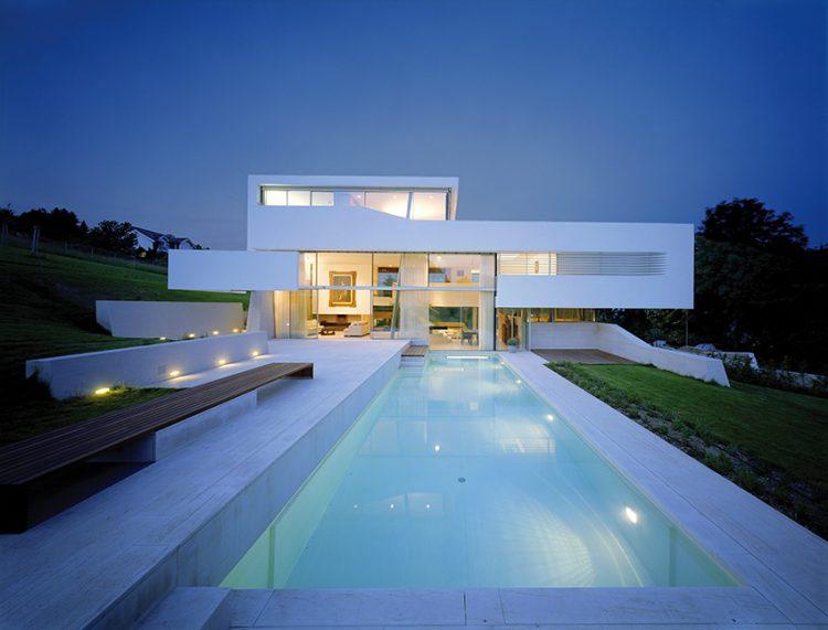 Zatímco přízemí rozlehlé rezidence kopíruje mírně svažitý terén, první a druhé patro vystupují ze stavební plochy a výraznými horizontálními liniemi charakterizují minimalistickou stavbu.