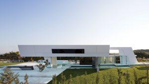 Horizontální linie architektury zpestřují zešikmené prvky, které stavbě vtiskují dynamický pocit. Z uliční zóny se do vily vchází po mostku z kamenných kvádrů.