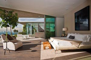 Ložnice majitele je umístěna v nejvyšší úrovni, za příznivého počasí ji lze propojit s terasou umístěnou nad bazénem. Skleněné zábradlí umožňuje nerušené výhledy.