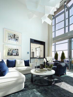 Bílá pohovka ve tvaru L i modré sofa jsou čalouněny látkou z produkce vyhlášené textilky Osborne & Little. Skvěle vynikají v kontextu s modrým kobercem od americké firmy BC&N Carpet.