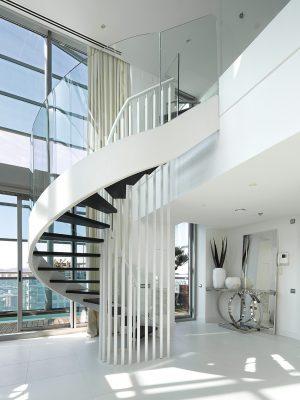 Ladné linie točitého schodiště vedoucího do horní partie bytu jsou jednou z dominant interiéru. Nápaditý středový prvek z bílé tyčoviny funguje zároveň jako vnitřní zábradlí, z boku stupně stoupající nahoru lemují tabule z transparentního skla.