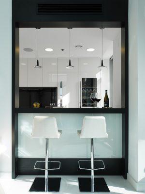 """Kuchyně je samostatná, se společenskou zónou apartmánu ji propojuje pouze """"podávací"""" otvor se širokým pultem, který funguje také jako bar. Otočné čalouněné stoličky jsou z produkce Ziru."""