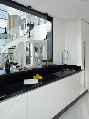 Kuchyňský nábytek s povrchem ve vysokém laku byl vyroben podle návrhu Molins Interiors. Závěsná svítidla Kin nad pracovní plochou z produkce firmy Oluce ladí s černo-bílou barevností kuchyně.