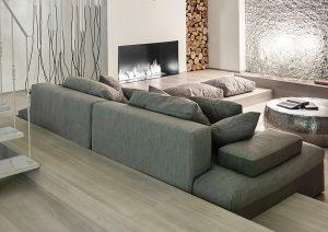 Odpočinková zóna s televizí je zapuštěna do podlahy obložené dřevem. Vzniklé sokly posloužily nejen k ukotvení pohovky, ale úspěšně sehrávají také roli schůdků, stejně jako netradičních odkládacích ploch.