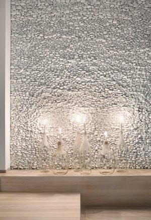 """Bílé oblázky, jejichž struktura vyniká zejména při nasvícení, dekorují """"televizní"""" stěnu ve společenské části bytu. Jednotlivé kamínky byly pečlivě ručně lepeny jeden po druhém, celá realizace trvala tři týdny."""