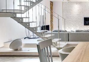 Odlehčené schodiště, jež se lehce vznáší v prostoru, pouze náznakem odděluje odpočinkovou část společenského přízemí od kuchyně s jídelnou.