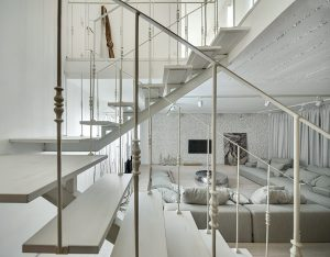 Subtilně působící páteřní schodiště s technicistní svařovanou kovovou konstrukcí a dřevěnými nášlapy nebrání díky svému pojetí v průhledech obytným prostorem.