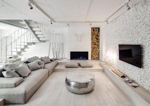 """Různé textury použité k realizaci stěn sehrávají při adekvátním nasvícení zejména roli dekorativních akcentů. Týká se to i niky, vyplněné dřevěnými poleny. Původní otevřené topeniště se totiž ukázalo jako nefunkční, takže bylo nahrazeno biokrbem od ukrajinského výrobce LEKS. Kovový """"bubnový"""" stolek z tepaného hliníku a kovu je od značky Deco 79."""