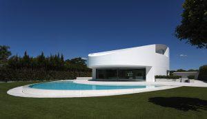 Oslnivě bílá fasáda zjemňuje hmotu budovy. Provedení kompozitním materiálem umožnilo architektovi obložení bez viditelných spojů a spár.