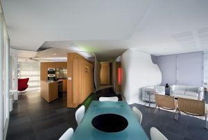 Zdánlivý chaos organických tvarů usměrňuje přísná geometrie nábytkových stěn. Jídelní stůl v centru apartmánu je umístěn v ose hlavní komunikace