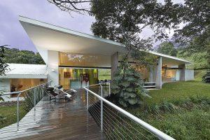 Rezidence podlouhlého tvaru kopíruje mírný svah na zatravněném pozemku tak, aby zúročila maximum výhledů do inspirativního okolí. Visutá terasa, navazující na společenské srdce domu, patří k oblíbeným místům relaxace. Trávit je lze například v komfortních ikonických lehátkách Le Corbusier, čalouněných pony kůží.