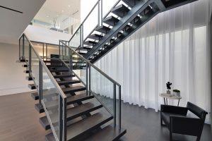 Obě podlaží domu spojuje vzdušné páteřní schodiště s kovovou samonosnou konstrukcí, nášlapy z masivního dřeva a zábradlím z bezpečnostního skla.