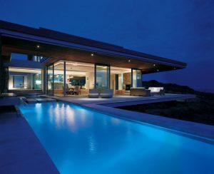 Osvětlená rezidence na břehu moře nechává při večerním nasvícení nahlédnout do interiéru. Luxusní a zároveň jednoduchý design s důrazem na přírodní materiály respektuje celkové architektonické řešení.