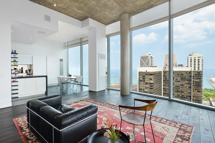 Minimalistický společenský prostor odděluje od kuchyně ostrůvek. kombinující mahagonový povrch s bílým lakem. Kožené křeslo LC2 od Le Corbusiera si hoví na perském koberci.