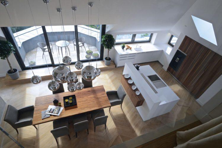 Vysoké stropy mezonetu ve střešní nástavbě posloužily jako ideální odrazový můstek pro velkorysé řešení kuchyně a na ni navazujícího jídelního stolu.