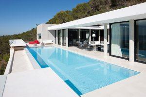 Velkorysý nekonečný bazén o rozměrech 12 x 5 m je součástí hlavní terasy navazující na obytné prostory s atriem uprostřed. Výhradně černobílé vyznění rezidence podtrhují doteky červené, tady v podobě venkovního sofa.