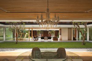 Do dalšího z dlouhých úzkých obytných bloků rezidence umístili projektanti jídelnu s kulatým stolem se skleněnou vrchní deskou. Výrazným dekorativním prvkem je křišťálový lustr.