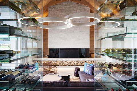 Prosklenou vinotékou je ze salonu vidět do hlavní společenské místnosti s dominantní krbovou stěnou, obloženou štípaným vápencem. Výraznou roli hraje lustr tvořený dvěma spojenými hliníkovými kruhy s LED zdroji.