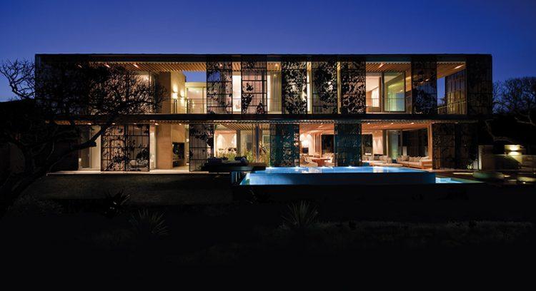 Průčelí rezidence směřující k oceánu zdobí posuvné panely z eloxovaného hliníku v bronzové barvě, jež však zároveň chrání dům před zdejším nepředvídatelným počasím. Jejich grafické ztvárnění prozrazuje inspiraci siluetami Milkwood stromů.