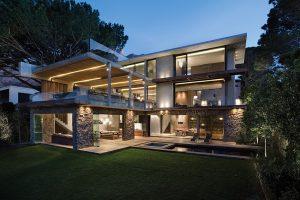 Dvě terasy nad sebou jsou ohraničené skleněným zábradlím, které maže hranice mezi interiérem a exteriérem. Také v nejnižší úrovni máte dojem, že jste v přírodě. Skládací skleněné stěny otevírají odpočinkový kout do zahrady s bazénem.