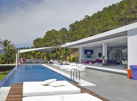 Terasu letní vily osvěžuje nekonečný bazén, obložený mozaikou Sicis v jasně modrých tónech. Venkovní jídelní stůl s masivní teakovou deskou a ocelovou podnoží je dílem místního tesaře.